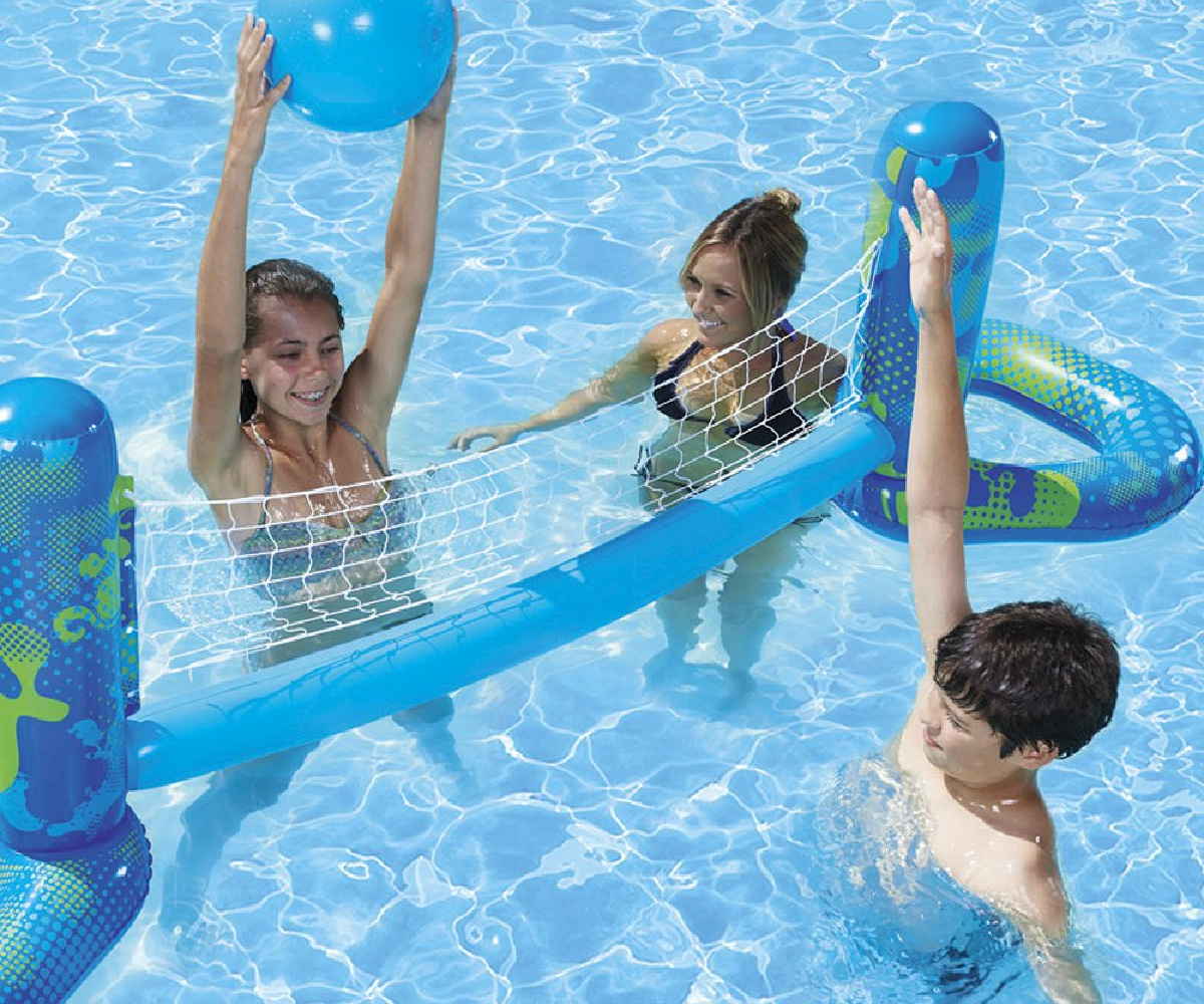 young boy and girls playing inflatable volleyball set in a pool