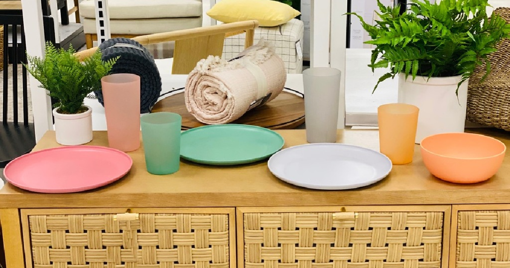 pink plate and cup, green plate and cup, gray plate and cup, and orange plate and cup on dresser in store