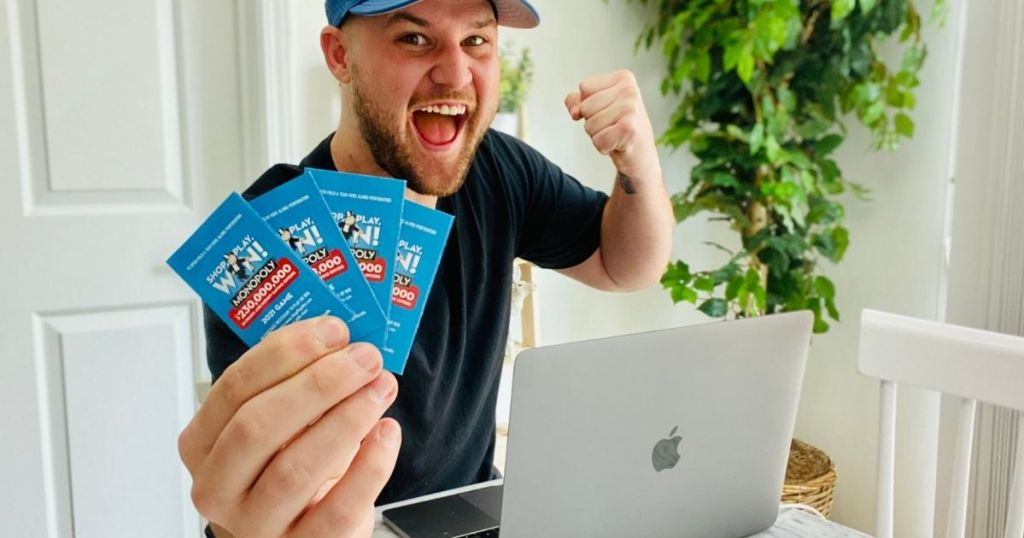 man holding Monopoly game tickets