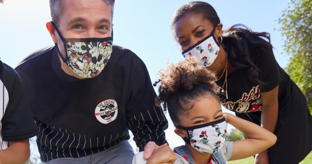 man, woman, and child wearing minnie mouse and mickey mouse face masks