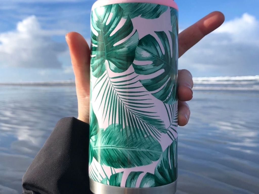 Slim Can Cooler in person's hand in front of ocean