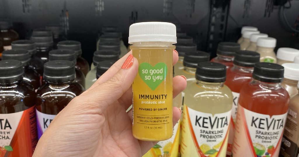 woman's hand holding immunity boost juice shot in store