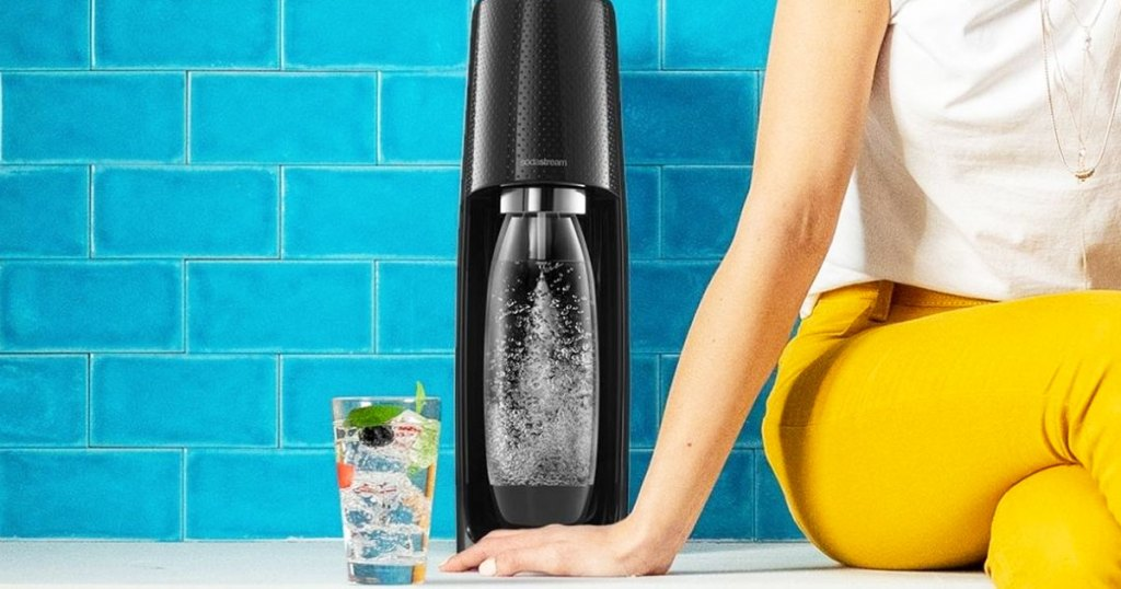 woman sitting on counter next to black sodastream machine making sparkling water