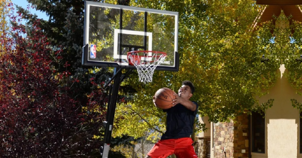 boy jumpng in the air making a shot at a basketball hoop