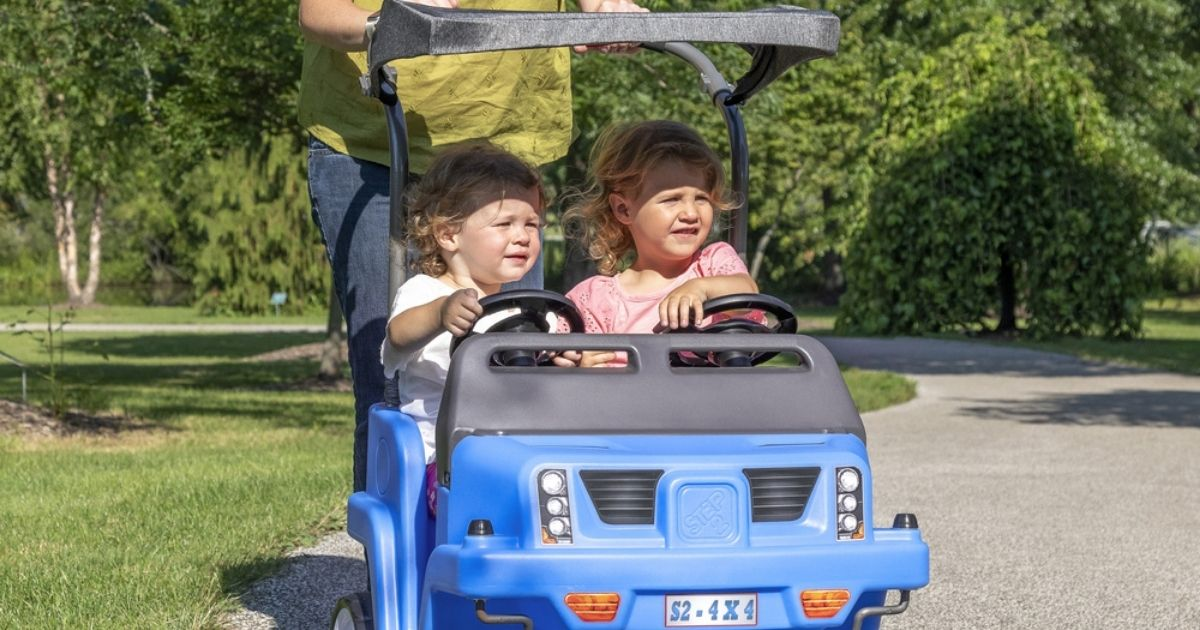 2 kids in a Step2 2-Seat SUV with lady pushing