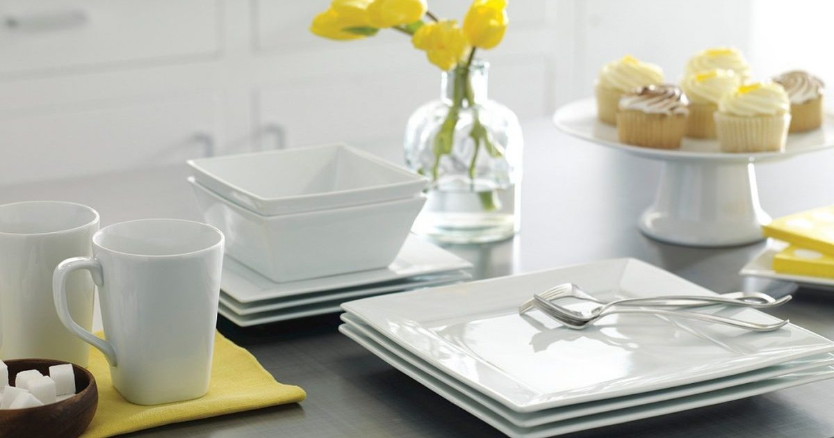 stacked white dishes on a kitchen island with flowers, cupcakes, and more items
