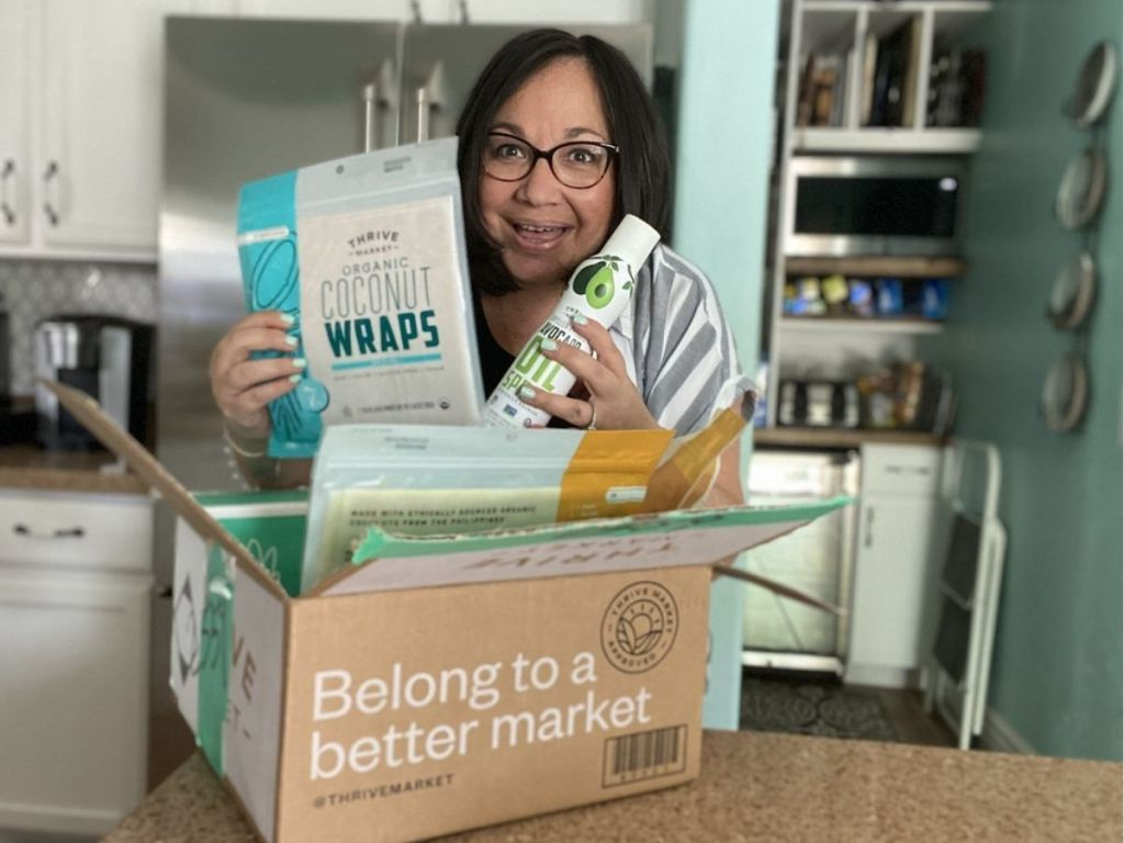 lady holding her thrive market box in a kitchen