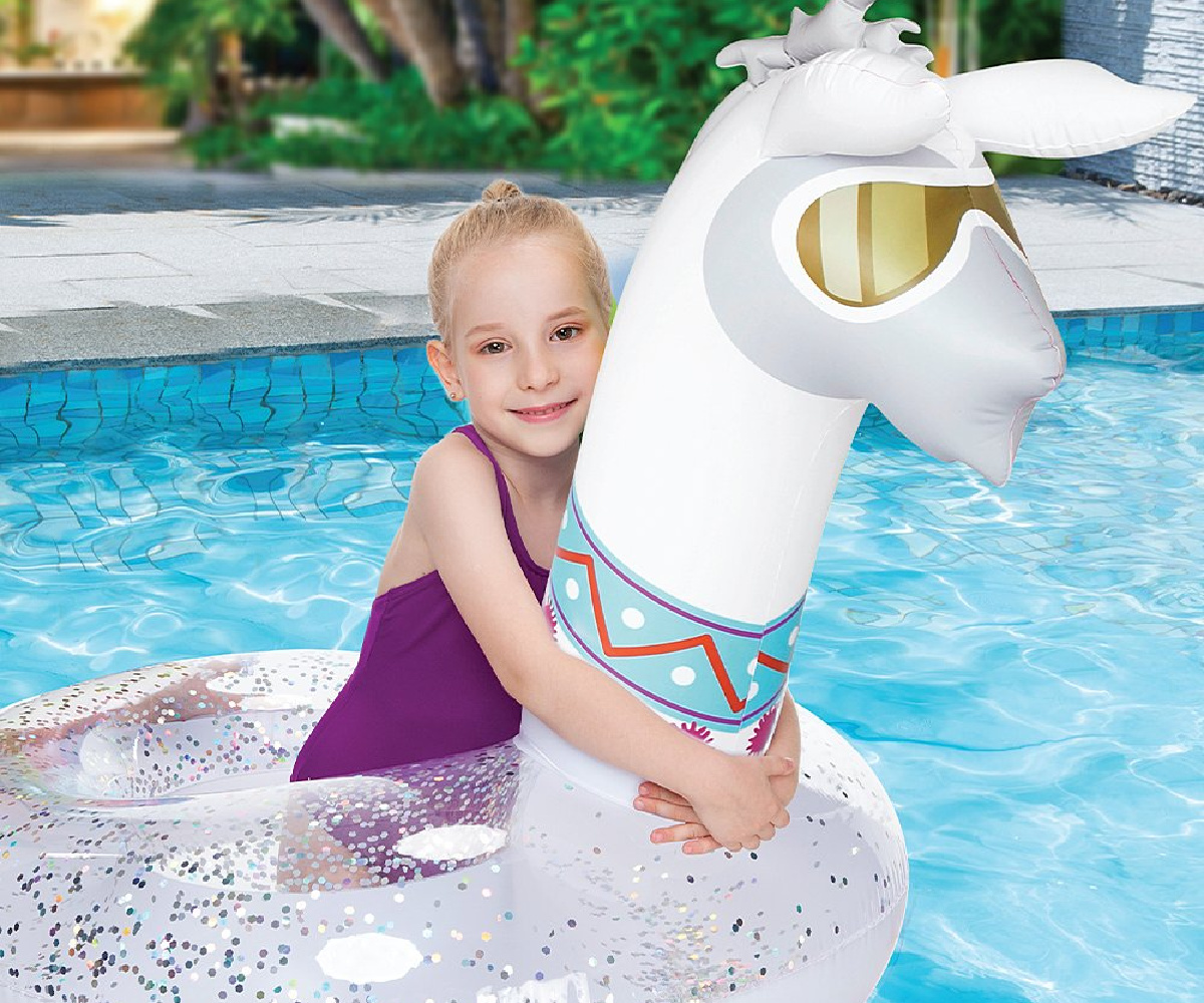 young girl in purple bathing suit on a glittery llama float in a pool