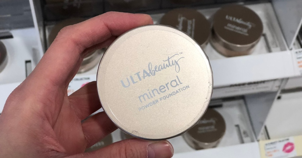 hand holding mineral powder foundation in store