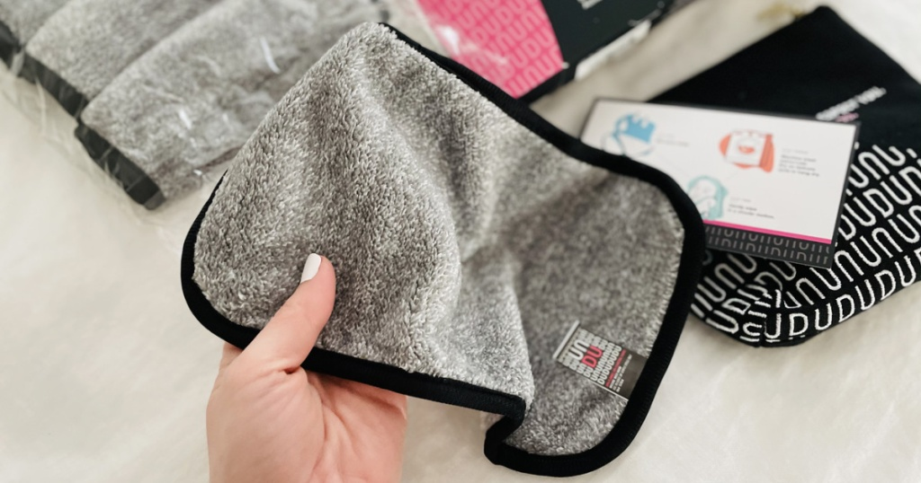 woman holding a gray face cleaning cloth