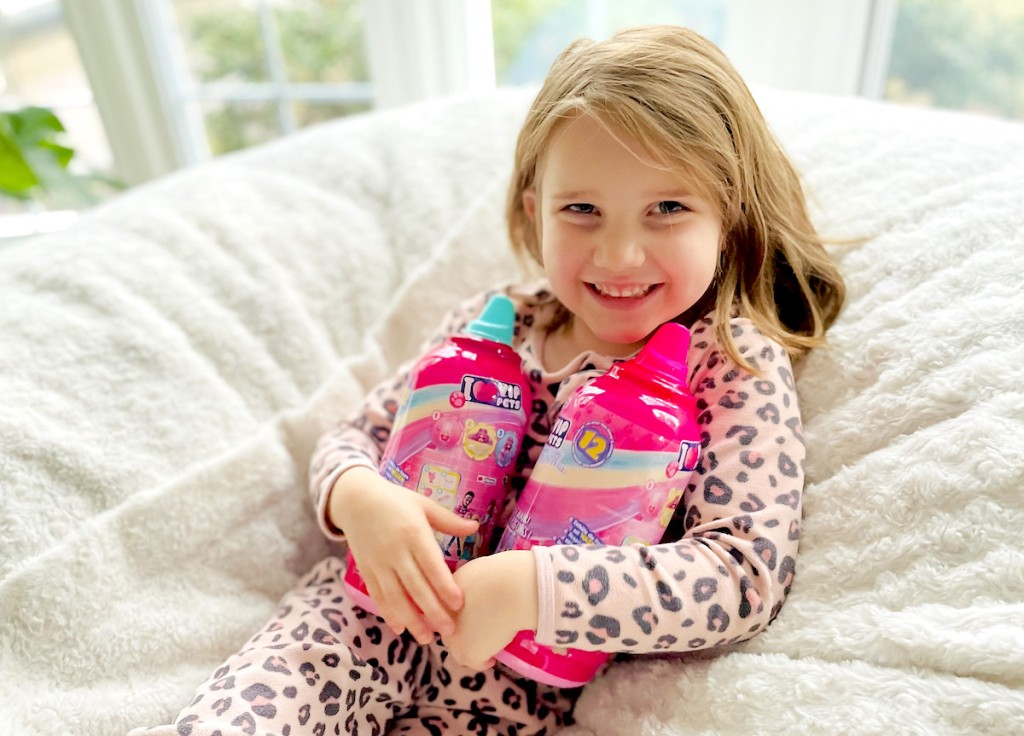 girl holding two vip pet doll surprise toys in hands smiling