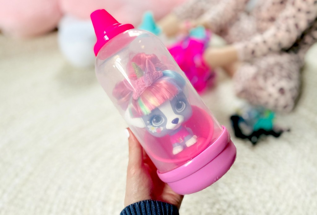 hand holding a VIP Pet doll in bottle