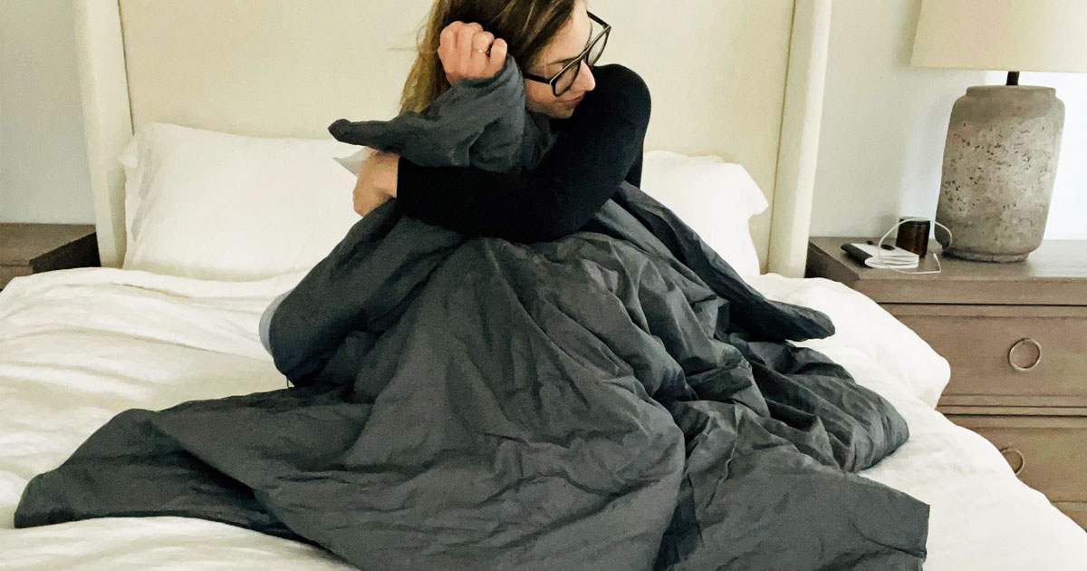 woman snuggling under grey weighted blanket
