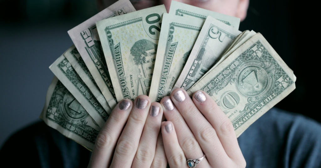 woman holding cash in front of face
