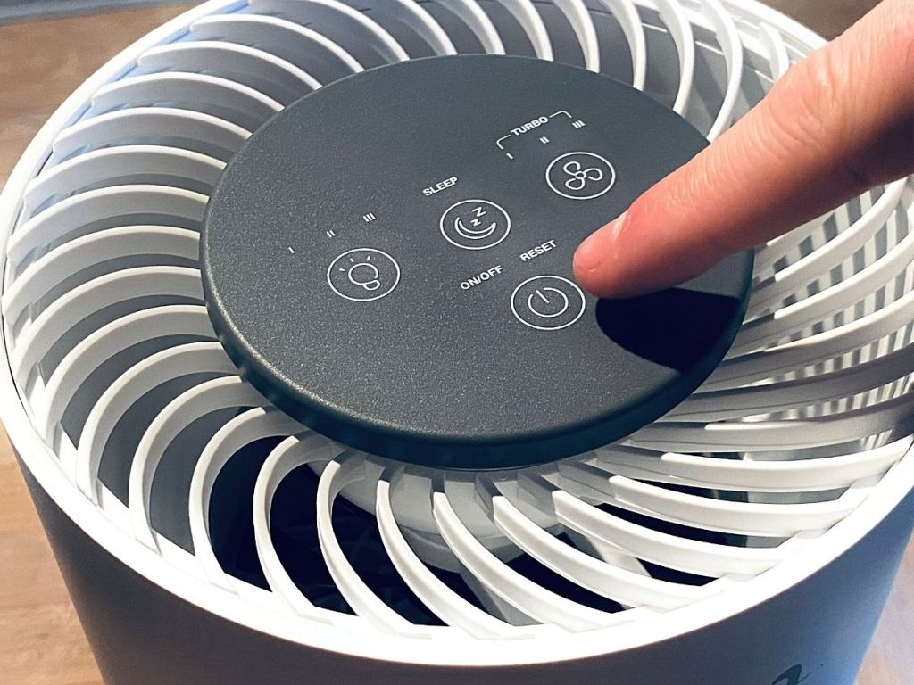 finger pointing at air purifier power button