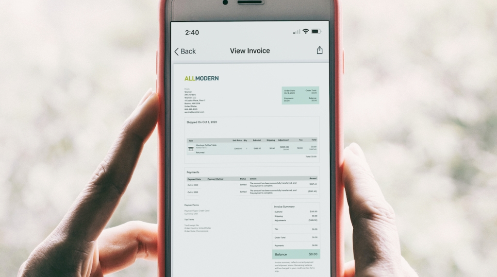 hands holding phone with all modern furniture return invoice on screen
