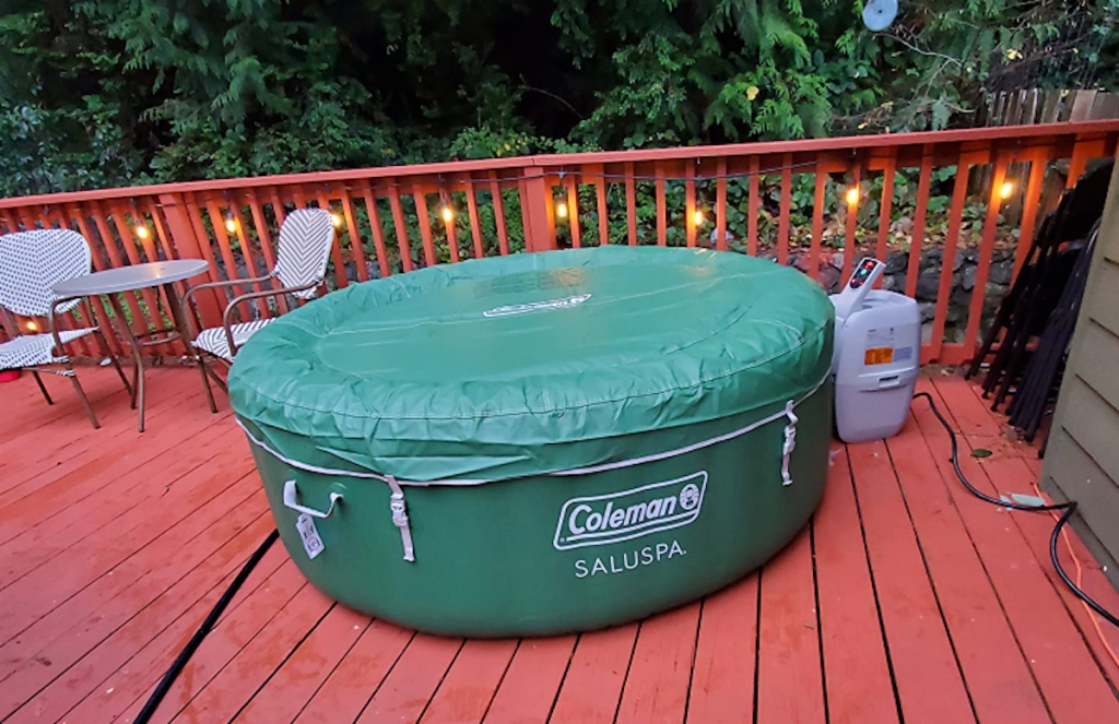 green coleman inflatable hot tub sitting on red deck with string lights