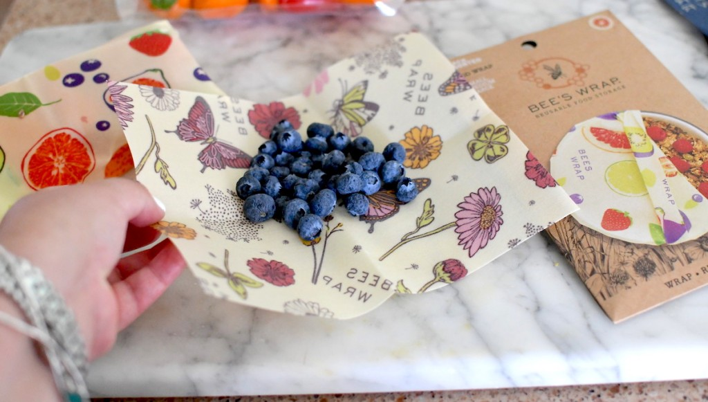 hand holding corner of bee's wraps reusable food wrap with blueberries