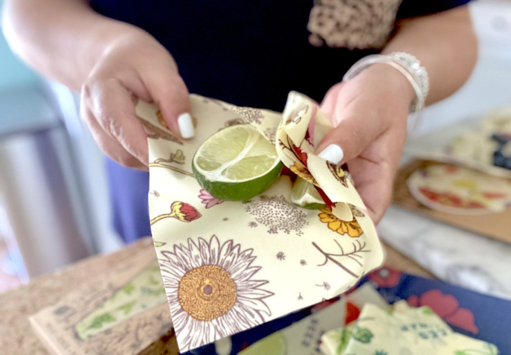 hands holding floral beeswax wraps with half but lime inside