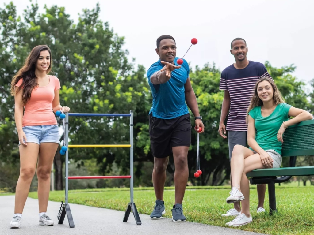 4 people playing ladderball outdoors