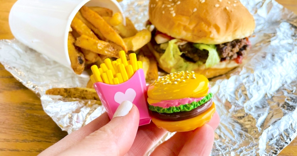 hand holding miniature fries and burger with five guys burgers in the background - April fools pranks