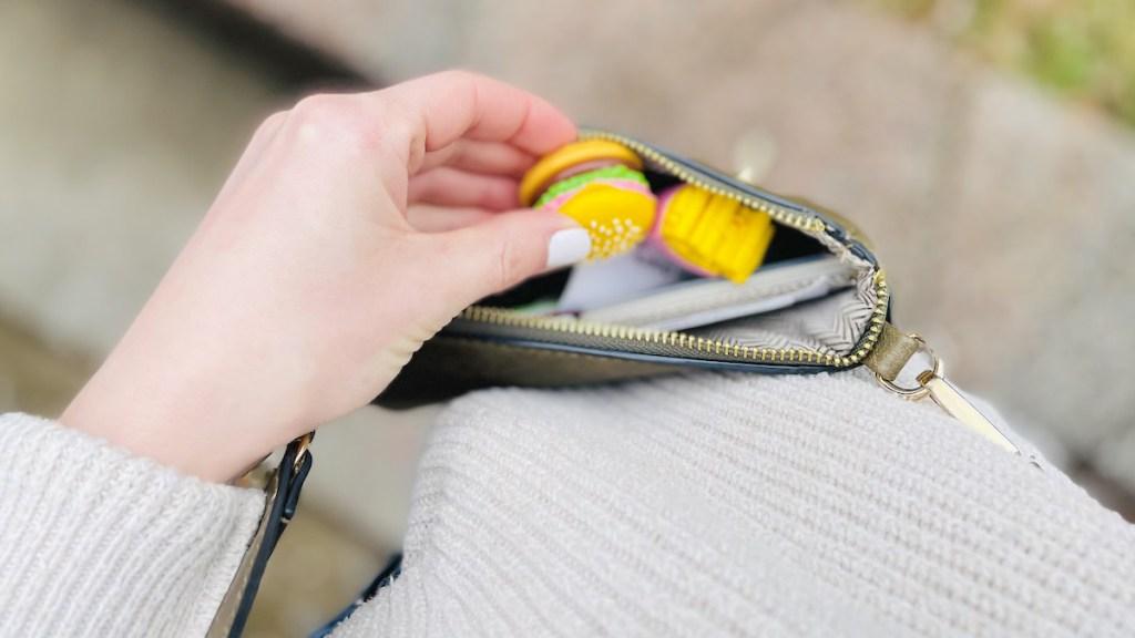 hand putting miniature burger in purse
