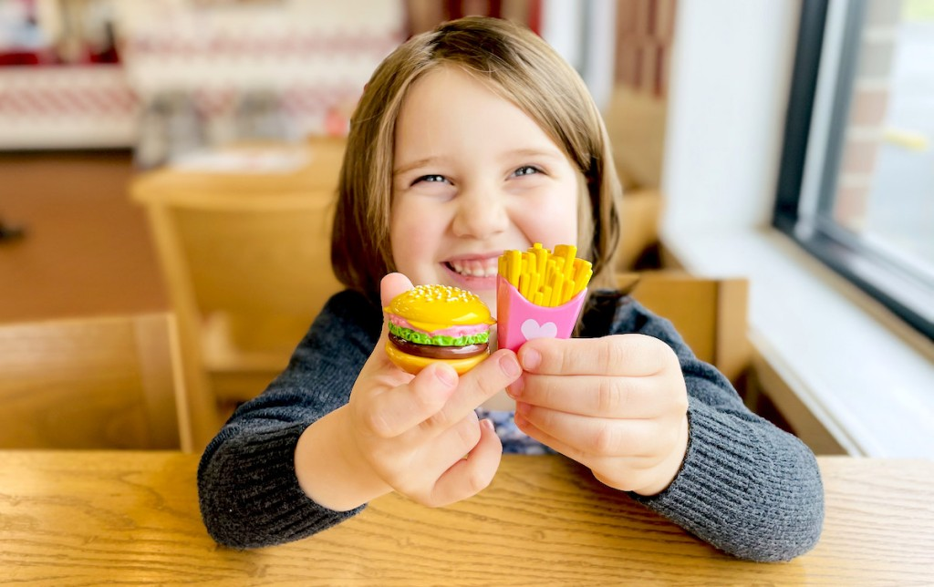girl smiling holding miniature burger and fries lip balm