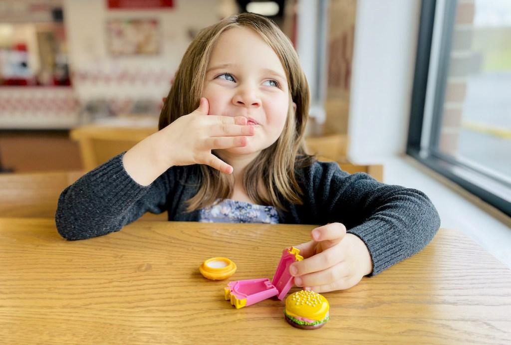 girl putting on lip balm sitting at table - April fools pranks