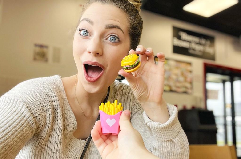 woman looking surprised holding miniature burger