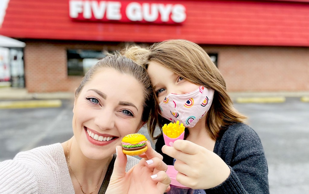 woman and girl standing outside of five guys holding mini burger and fries
