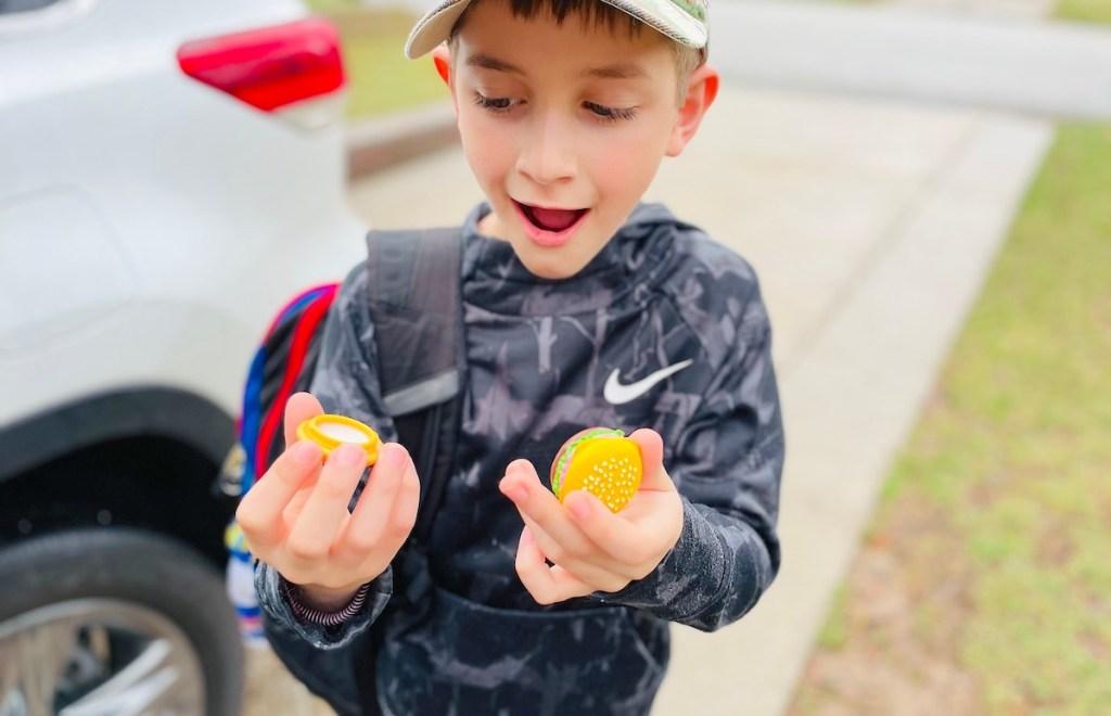 boy holding miniature burger lip balm outside - April fools pranks