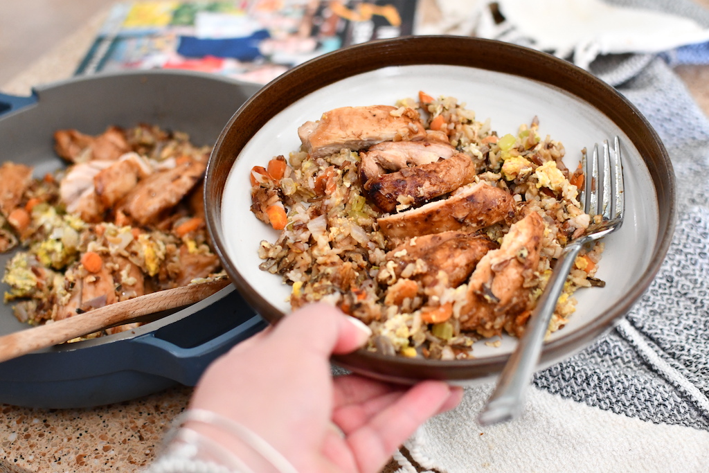 holding plate with sliced chicken and wild rice