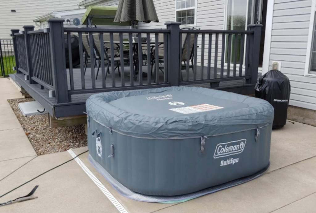 large square gray inflatable hot tub on concrete patio