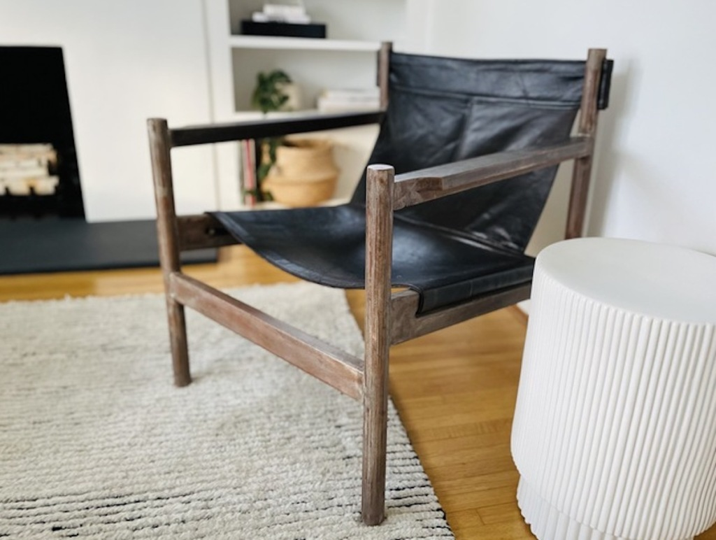 modern leather sling chair sitting in living room with white side table