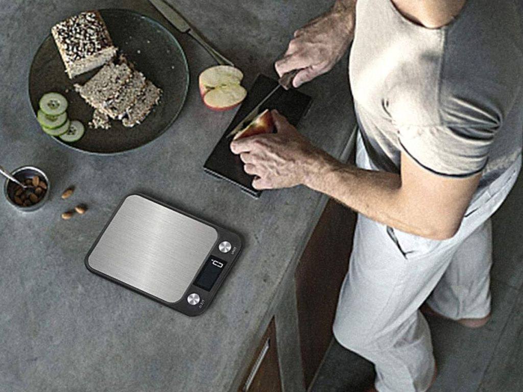 man chopping up apple next to digital food scale