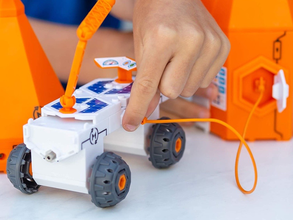 little hands pointing to circuit on small white and orange toy