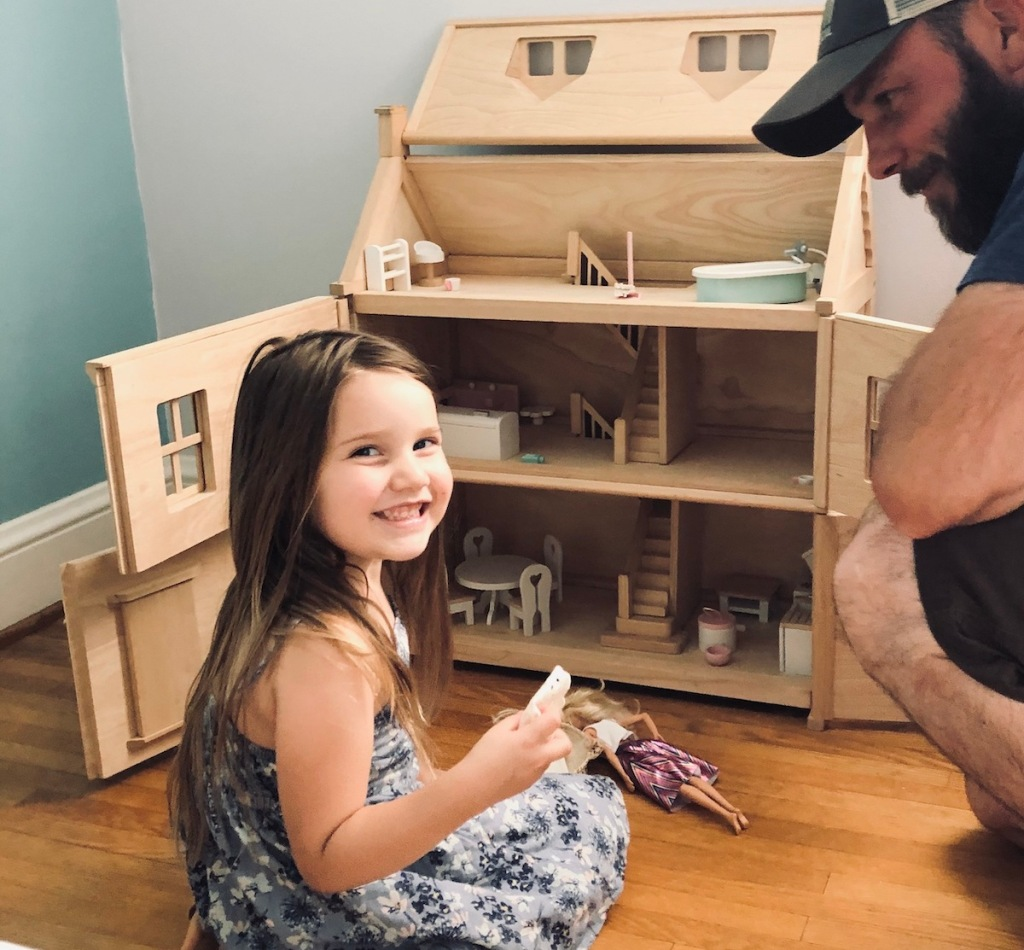 girl sitting in front of large wooden dollhouse