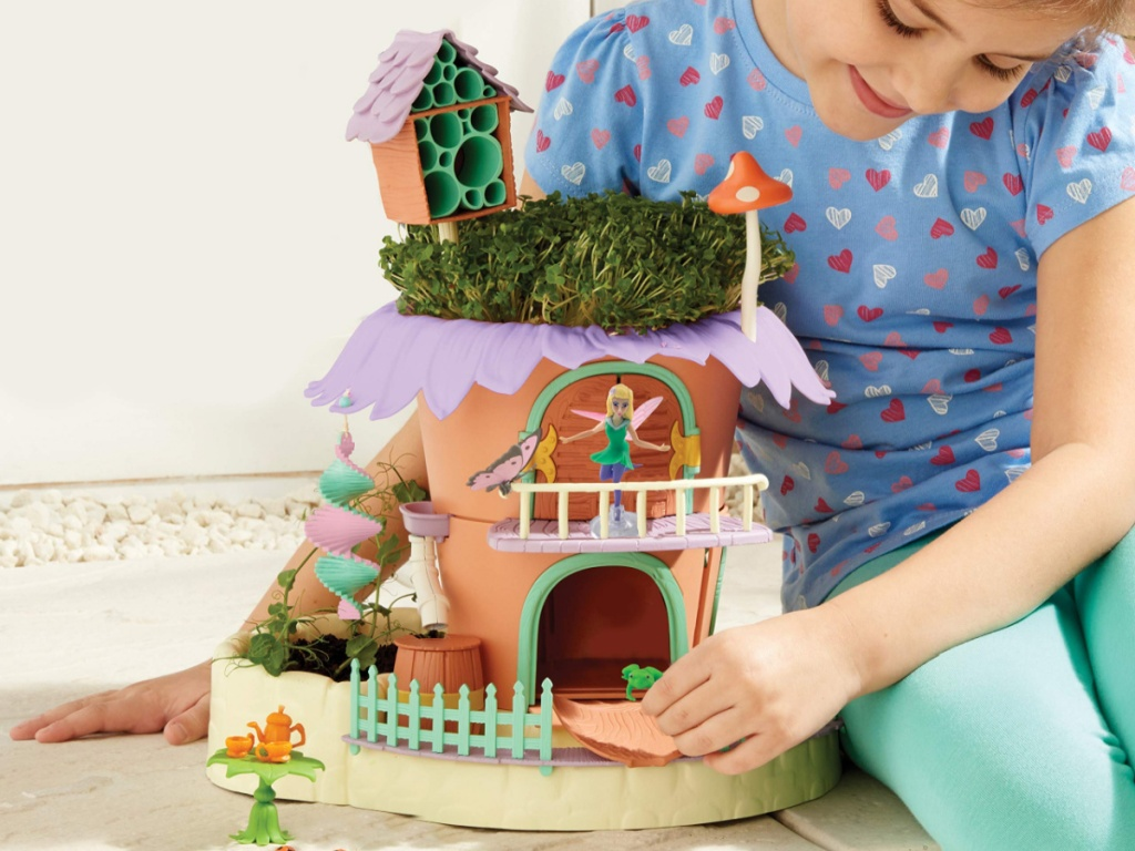 girl playing with fairy garden toy