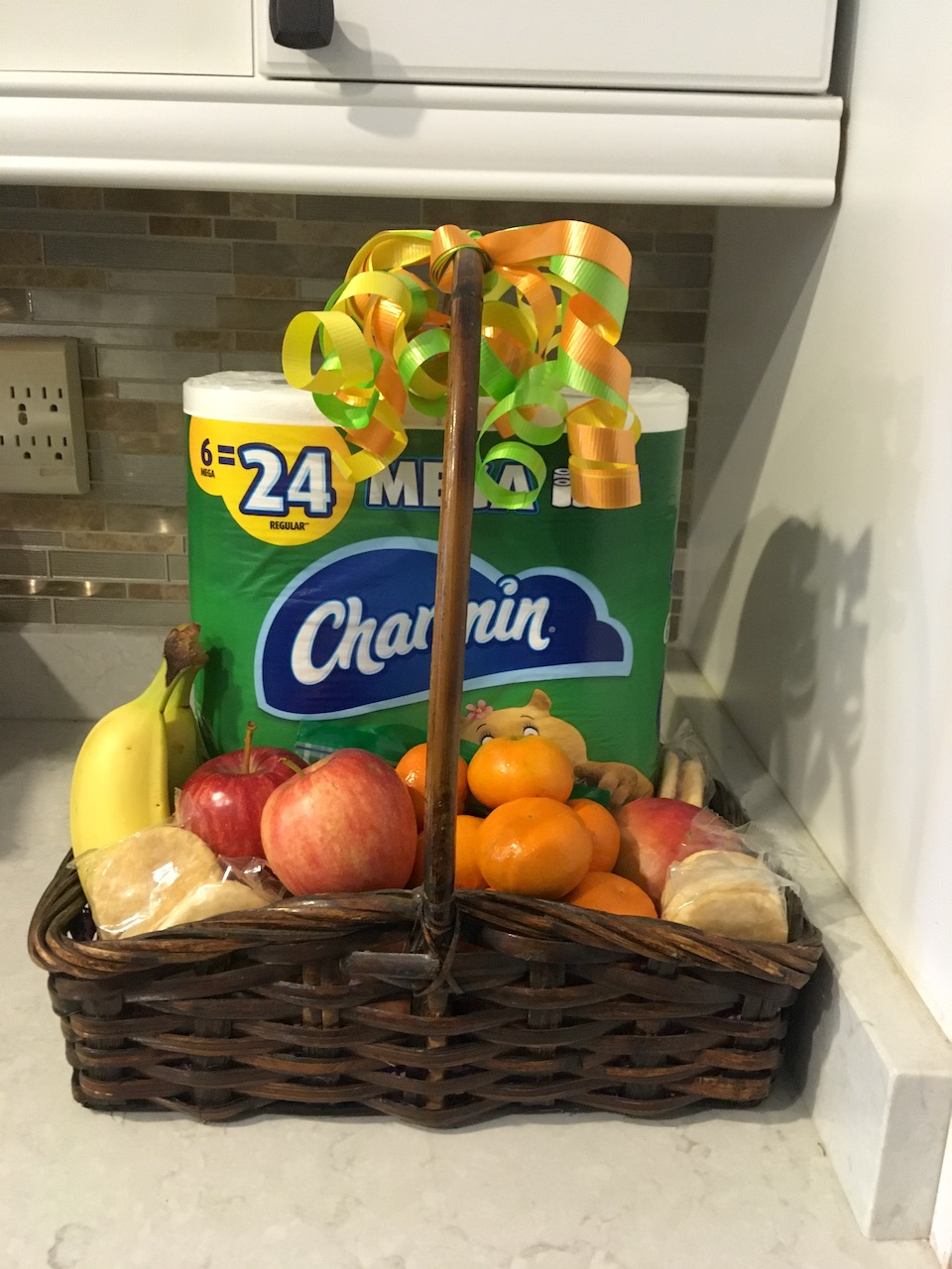 Gift basket filled with fruit and Charmin toilet paper