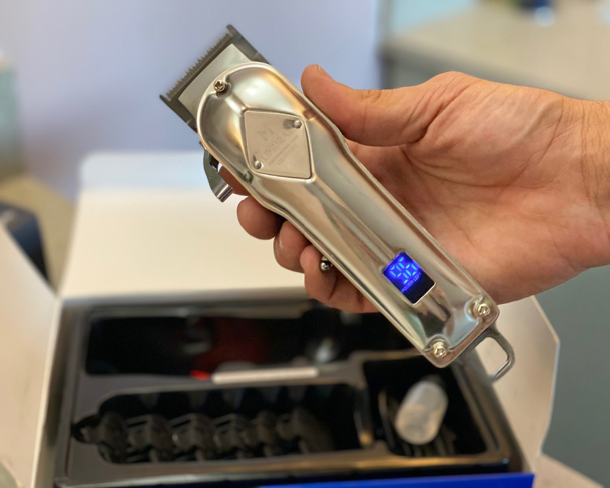 hair clippers in hand w/ LED screen