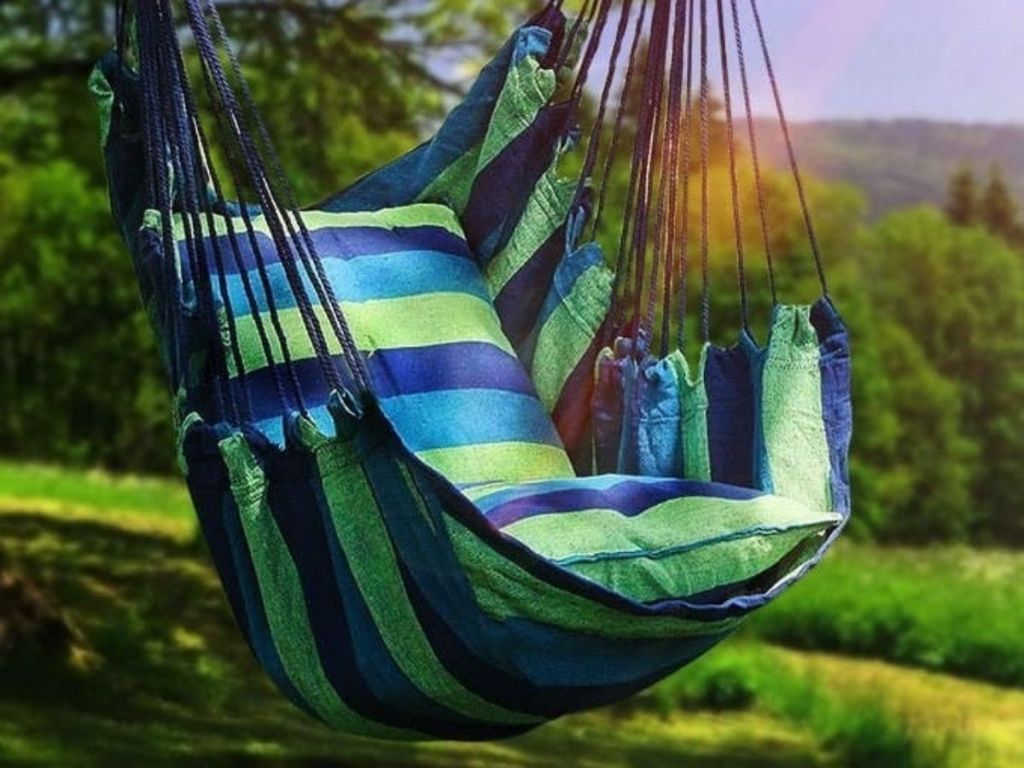 green and blue striped hammock hanging outside