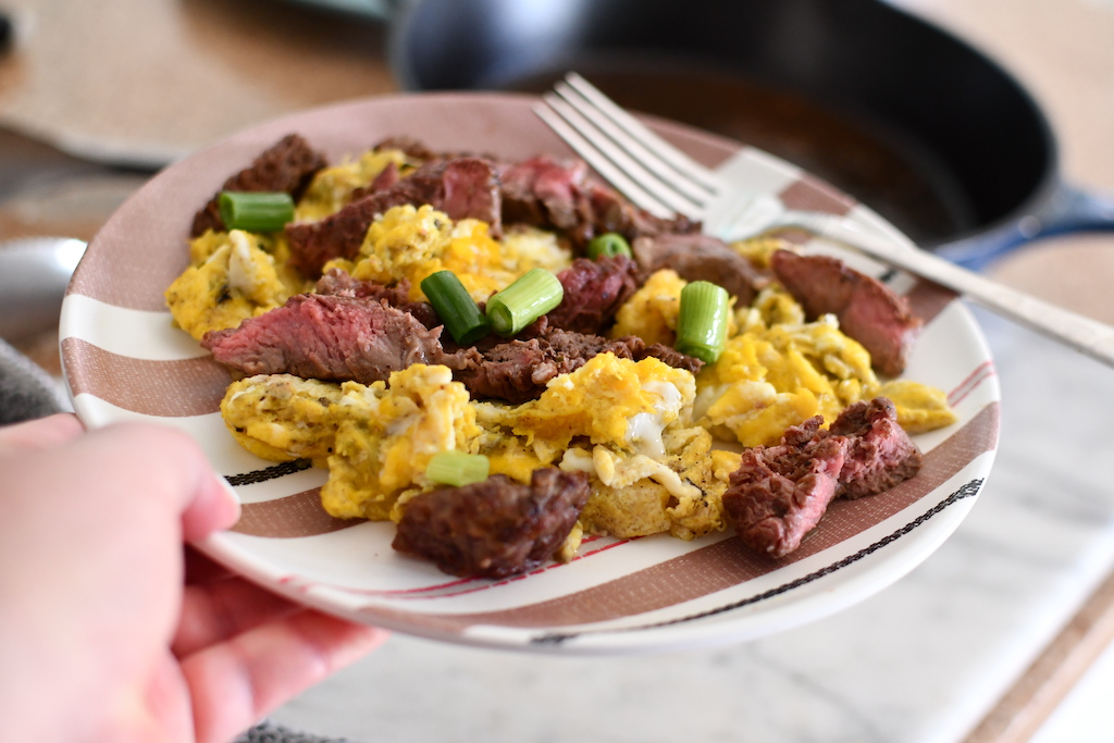 holding plate with scrambled eggs and steak slices