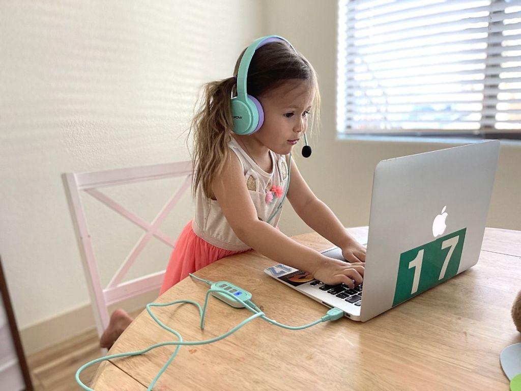 kid wearing headphone typing and staring at laptop