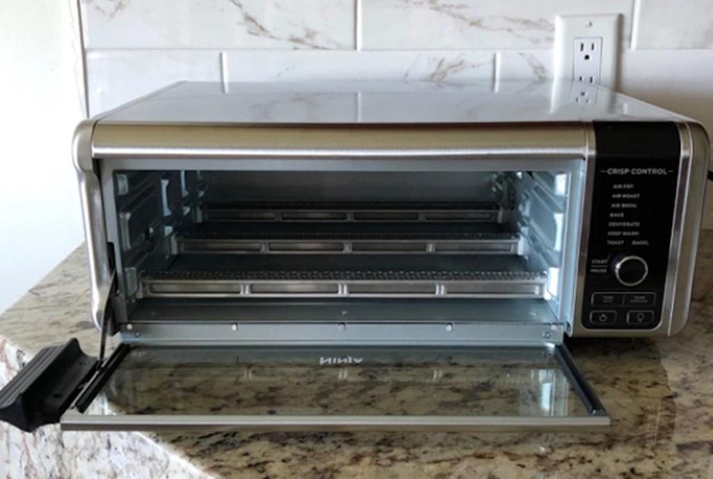 ninja air fryer oven on kitchen counter with glass door open