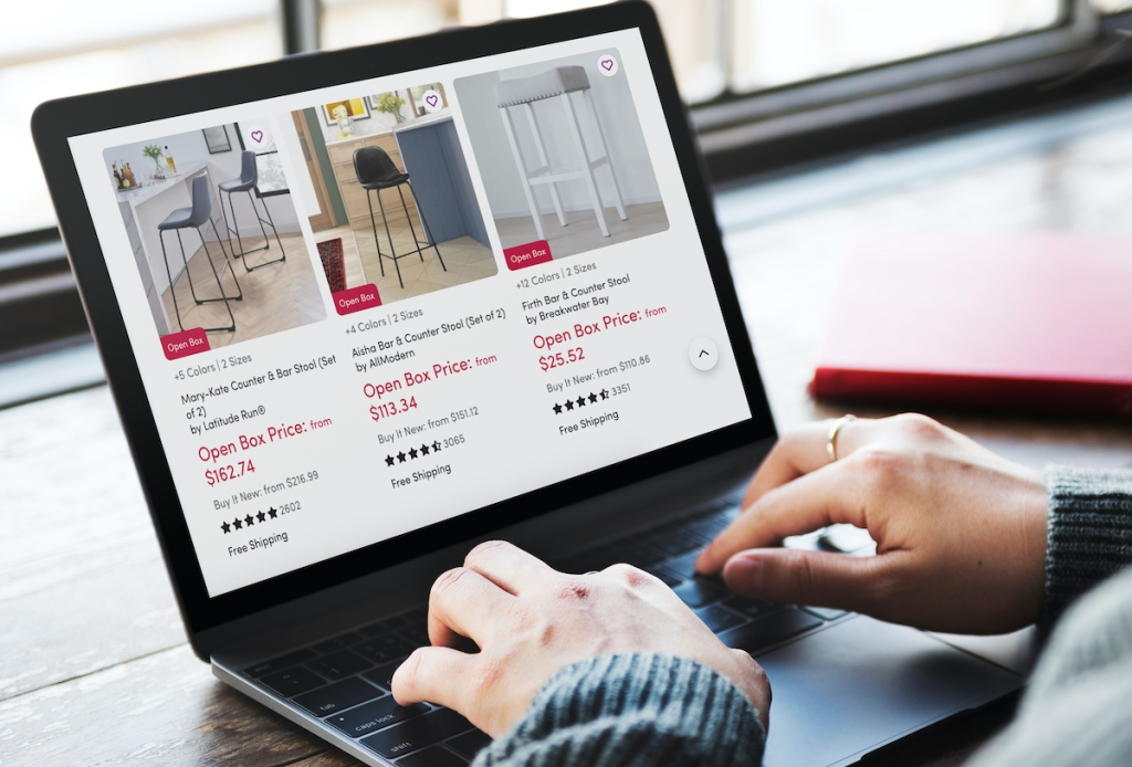 hands typing on laptop with open box furniture listings on screen home decor ideas