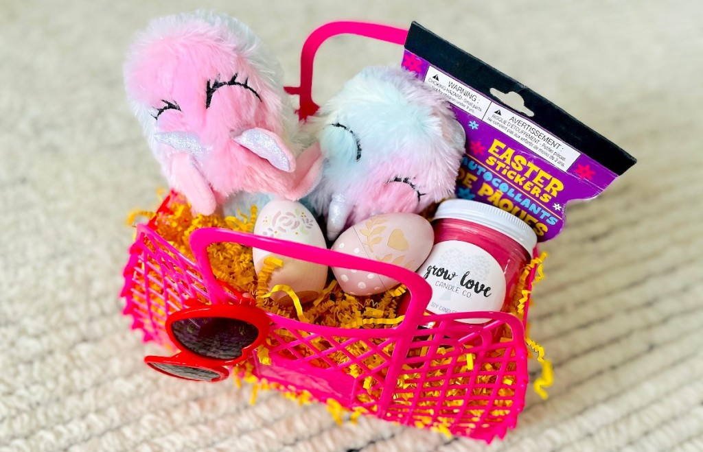 pink basket with easter stuff inside sitting on floor