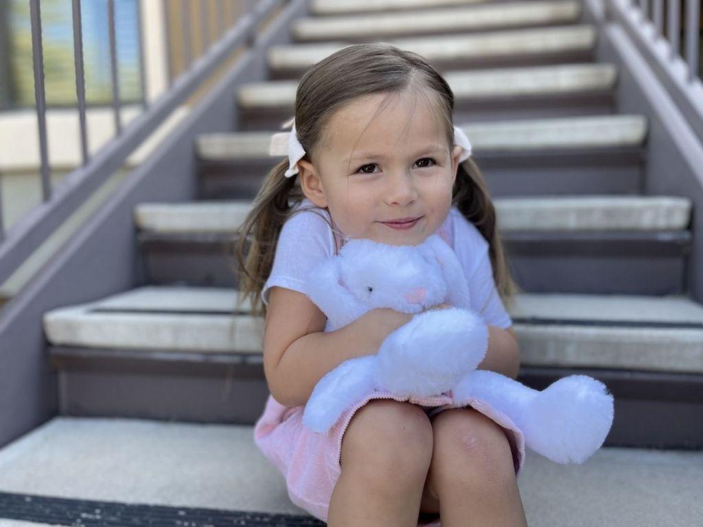 girl sitting on steps holding white bunny