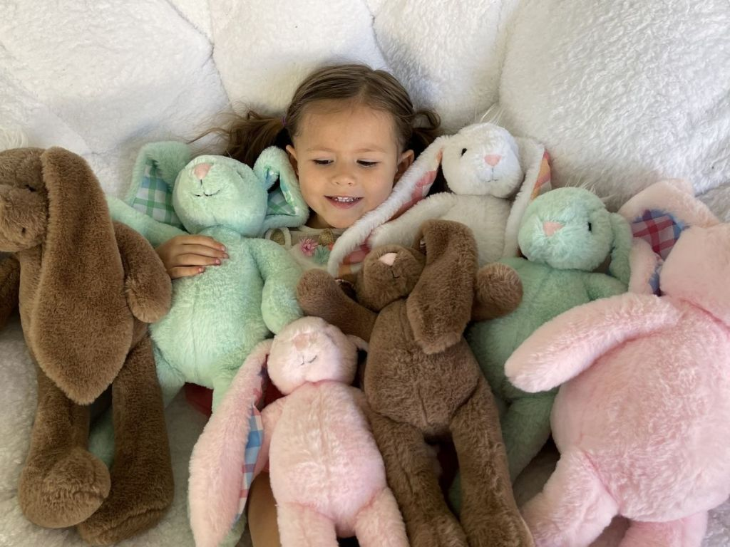 little girl in chair with lots of plush bunnies