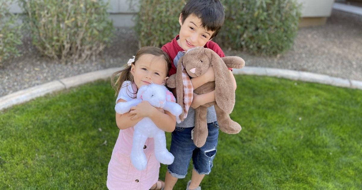 girl and boy hugging plush bunnies outside
