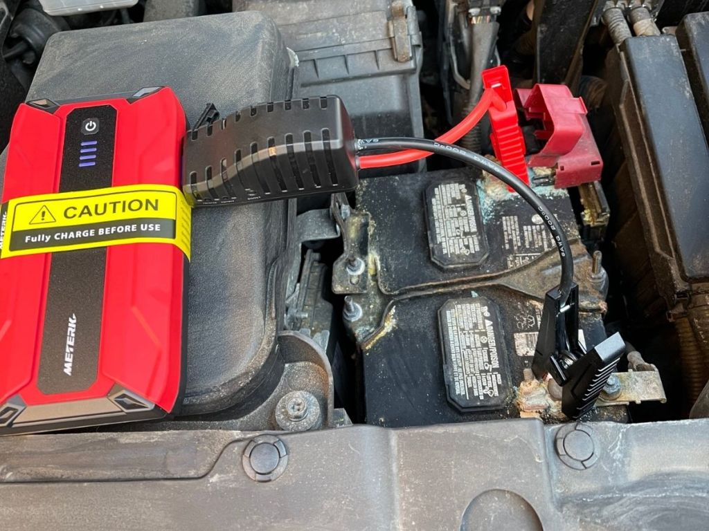 red and black portable jump starter on car engine